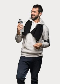 Hombre del deporte que sostiene una taza de café caliente sobre fondo gris aislado