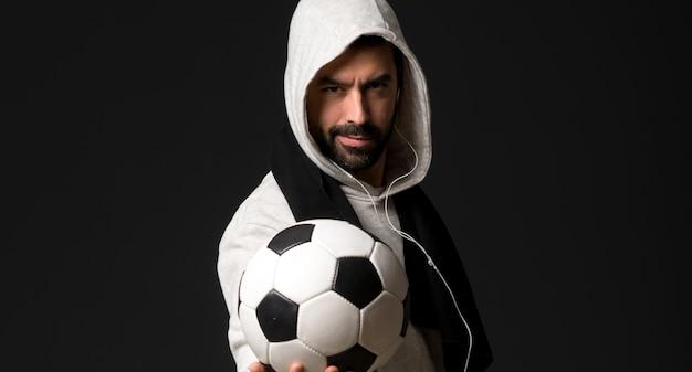 Hombre de deporte sobre fondo oscuro sosteniendo un balón de fútbol