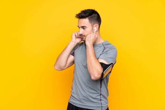 Hombre de deporte sobre música de pared amarilla aislada escuchando