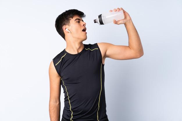 Hombre de deporte sobre pared azul con botella de agua deportiva
