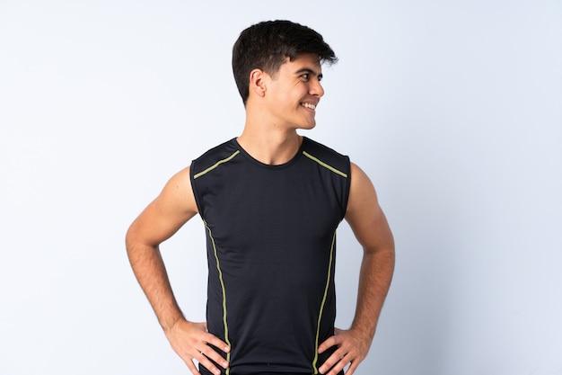 Hombre de deporte sobre pared azul posando con los brazos en la cadera y mirando hacia el lado