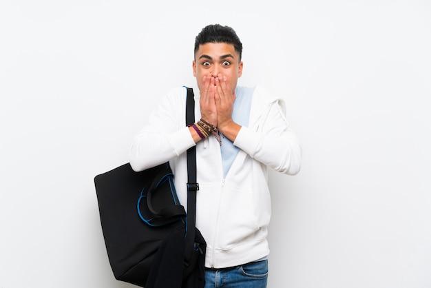 Hombre del deporte sobre la pared blanca aislada con expresión facial sorpresa