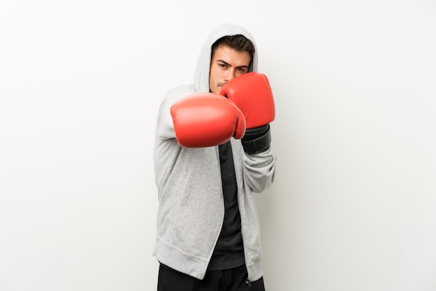 Hombre de deporte sobre pared blanca aislada con guantes de boxeo