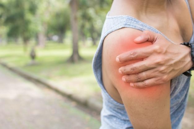 El hombre del deporte tiene dolor en el hombro o está herido y entrena como ejercicio en el parque