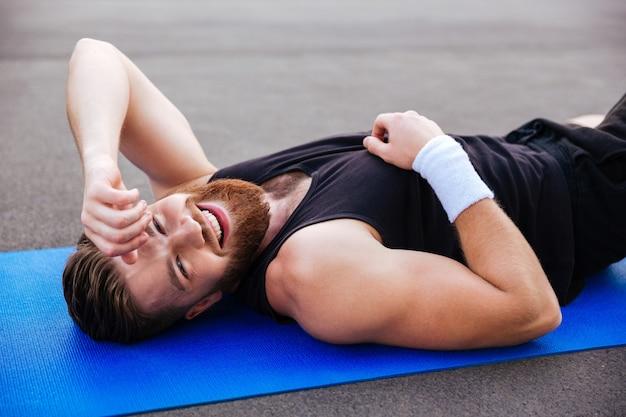 Hombre de deportes barbudo riendo alegre descansando sobre la estera de fitness azul al aire libre