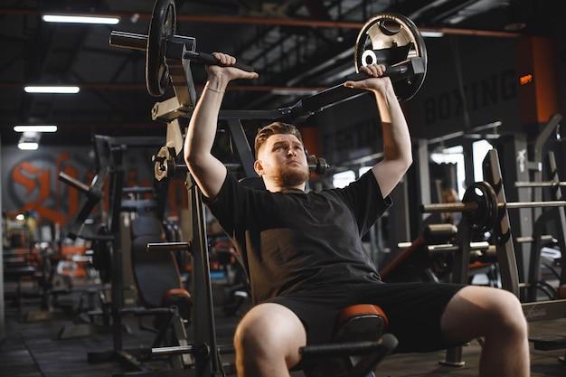 Hombre de deportes en el gimnasio. un hombre realiza ejercicios. chico en una camiseta