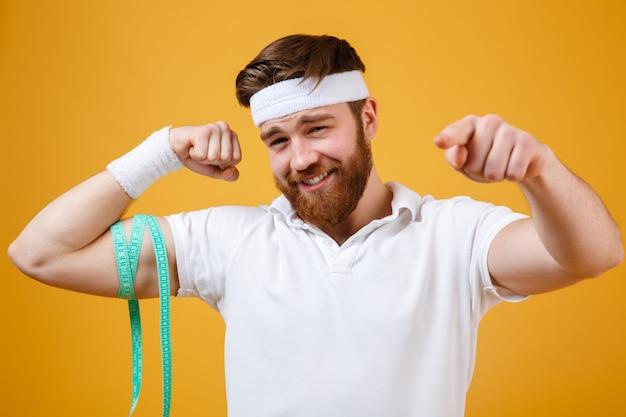 Hombre de deportes midiendo sus bíceps y apuntando con el dedo a la cámara