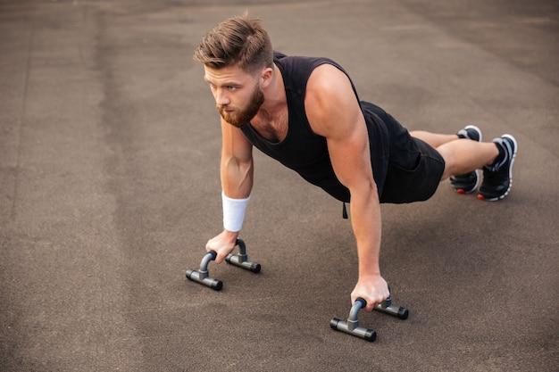 Hombre de deportes musculosos haciendo flexiones y usando equipos deportivos al aire libre