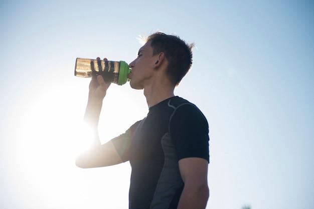 Hombre deportista cansado beber agua de una coctelera