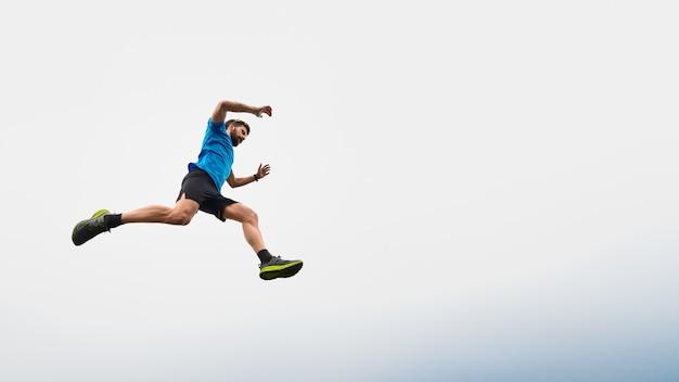Hombre deportista corriendo en las montañas durante un salto en el cielo