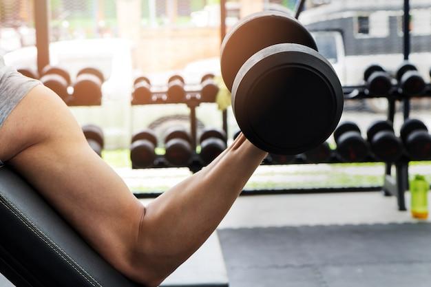 Hombre deportista entrenando en el gimnasio. un hombre levantando mancuernas - curl de bíceps con mancuernas