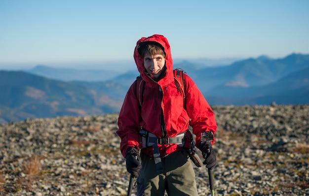 Hombre deportista excursionista en la cima de la montaña con hermosas montañas en el fondo