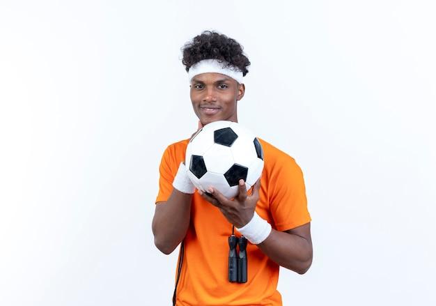 Hombre deportivo afroamericano joven complacido con diadema y muñequera sosteniendo la pelota con saltar la cuerda en el hombro