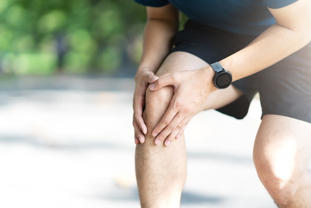 Hombre deportivo asiático joven que lleva a cabo dolor de la rodilla en parque de naturaleza público corriente