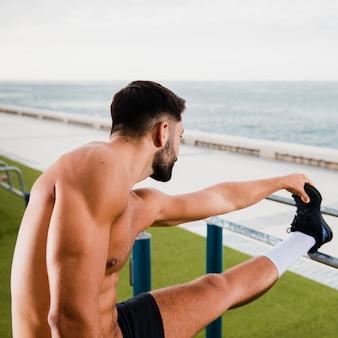 Hombre deportivo calentando antes de correr
