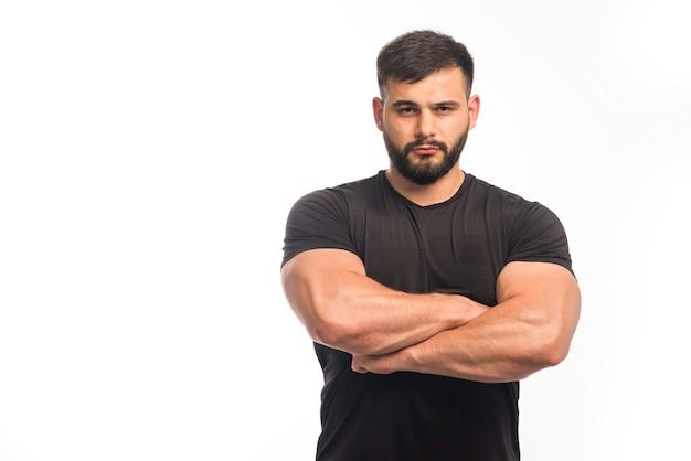 Hombre deportivo en camisa negra cerrando los músculos del brazo.