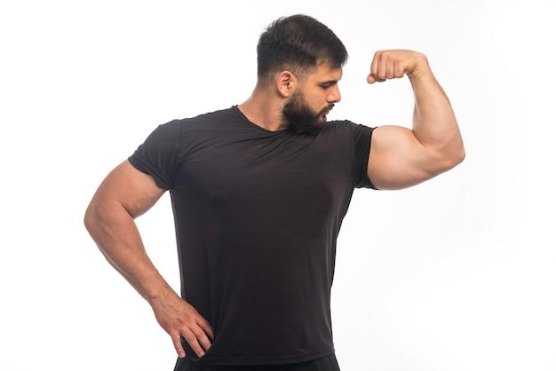 Hombre deportivo en camisa negra mostrando los músculos de su brazo