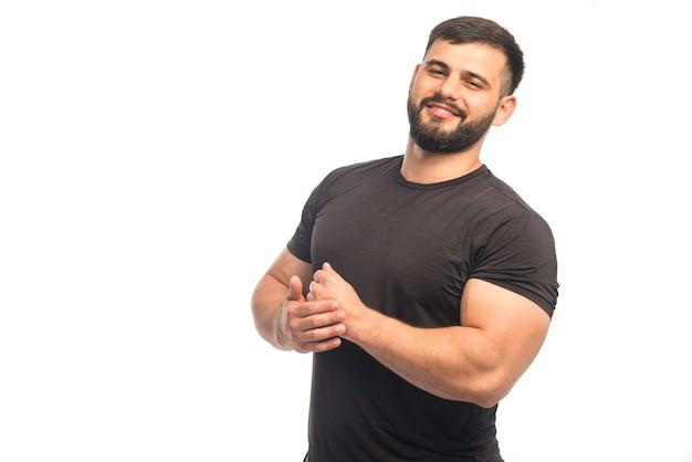 Hombre deportivo en camisa negra que demuestra los músculos de su brazo y parece positivo