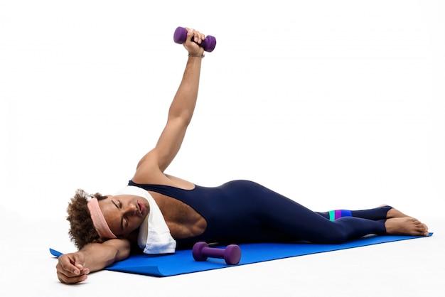 Hombre deportivo cansado acostado en la estera de yoga