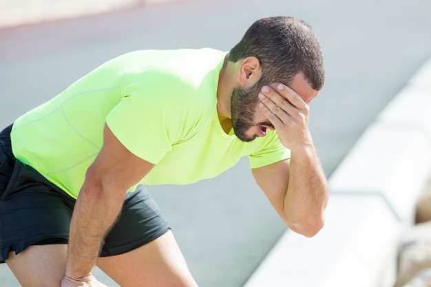 Hombre deportivo cansado que se relaja y que cubre la cara