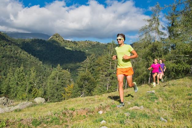 Hombre deportivo y chicas jóvenes corriendo juntos en la hierba en un mo