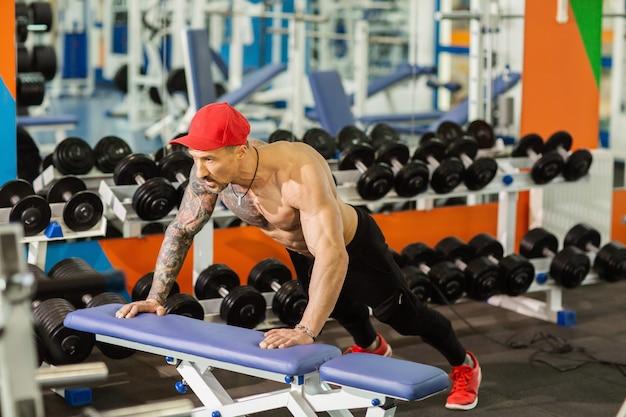 Hombre deportivo fuerte haciendo flexiones en el banco durante el entrenamiento en el gimnasio