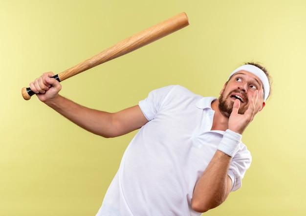 Hombre deportivo guapo joven asustado con diadema y muñequeras sosteniendo un bate de béisbol mirándolo con la mano levantada aislada en el espacio verde