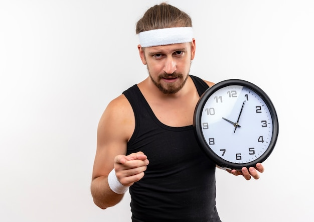 Hombre deportivo guapo joven confiado con diadema y muñequeras sosteniendo el reloj y apuntando aislado en la pared blanca con espacio de copia