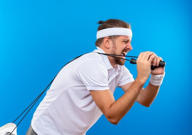 Hombre deportivo guapo joven disgustado con diadema y muñequeras de pie en la vista de perfil sosteniendo y tirando de la cuerda para saltar aislado en el espacio azul