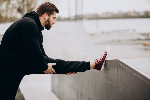 Hombre deportivo guapo que se extiende en el parque junto al río