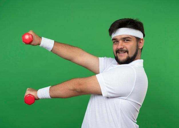 Hombre deportivo joven complacido con diadema y muñequera haciendo ejercicio con pesas aislado en la pared verde