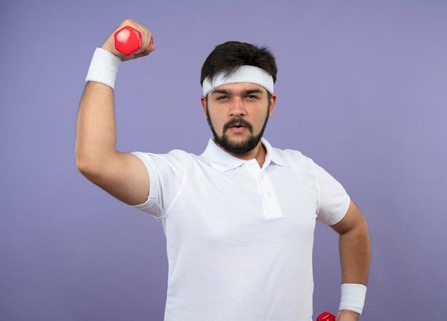 Hombre deportivo joven confiado con diadema y muñequera haciendo ejercicio con mancuernas aislado en la pared verde