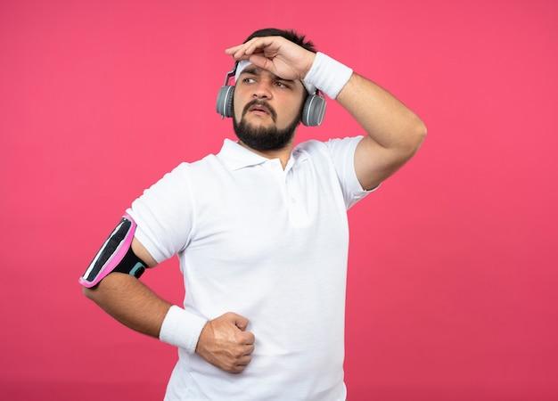 Hombre deportivo joven confidente con diadema y muñequera con auriculares y brazalete de teléfono poniendo la mano en la frente aislada en la pared rosa