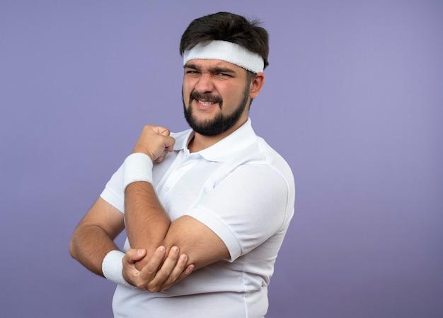 Hombre deportivo joven lesionado con diadema y muñequera agarró el codo dolorido aislado en la pared verde con espacio de copia