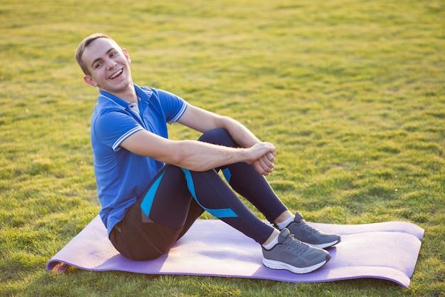 Hombre deportivo joven que se sienta en la estera de entrenamiento en campo de la mañana al aire libre.