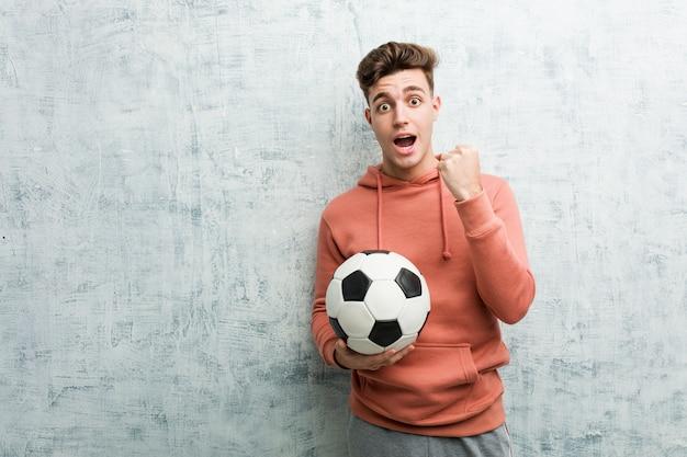 Hombre deportivo joven que sostiene un balón de fútbol que anima despreocupado y emocionado. concepto de victoria