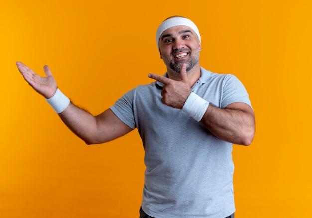 Hombre deportivo maduro en diadema mirando confiado apuntando con el dedo hacia el lado que presenta con el brazo de la mano de pie sobre la pared naranja