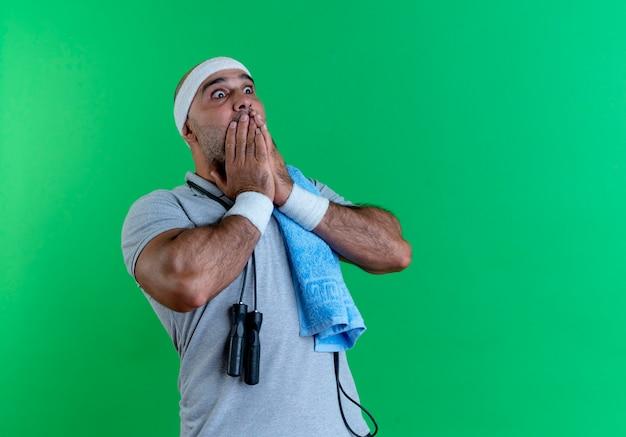Hombre deportivo maduro en diadema con una toalla alrededor de su cuello mirando a un lado conmocionado cubriendo la boca con las manos de pie sobre la pared verde