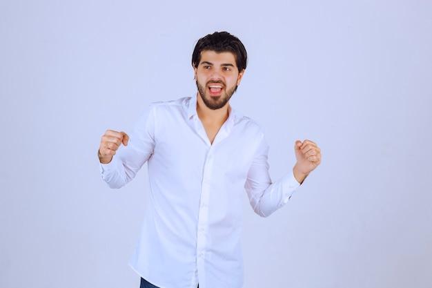Hombre deportivo mostrando los puños y sintiéndose poderoso.