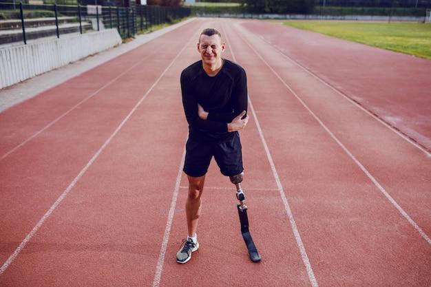 Hombre deportivo con pierna artificial de pie en pista de atletismo y dolor de estómago.