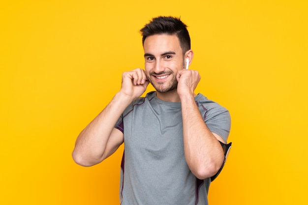 Hombre deportivo sobre pared amarilla escuchando música