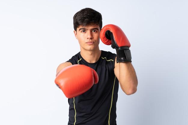 Hombre deportivo sobre pared azul con guantes de boxeo