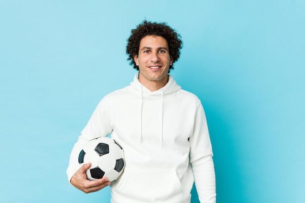 Hombre deportivo sosteniendo un balón de fútbol feliz, sonriente y alegre.