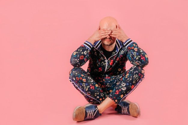 Hombre deprimido calvo en chándal de moda con las manos en los ojos en la pared de color rosa.