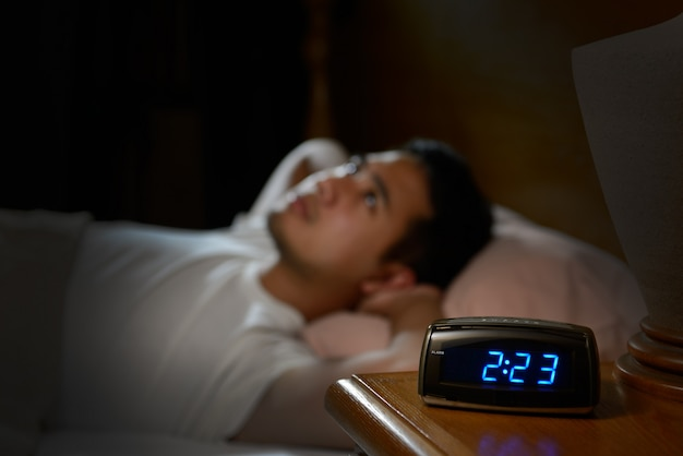 Hombre deprimido que sufre de insomnio acostado en la cama