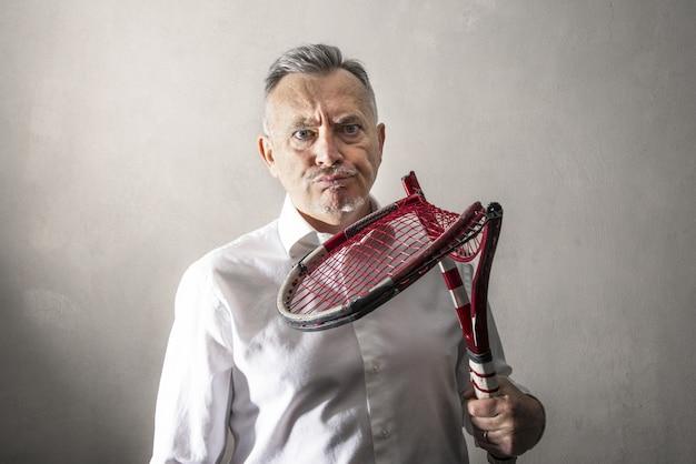 Hombre desanimado mirando su raqueta de tenis rota