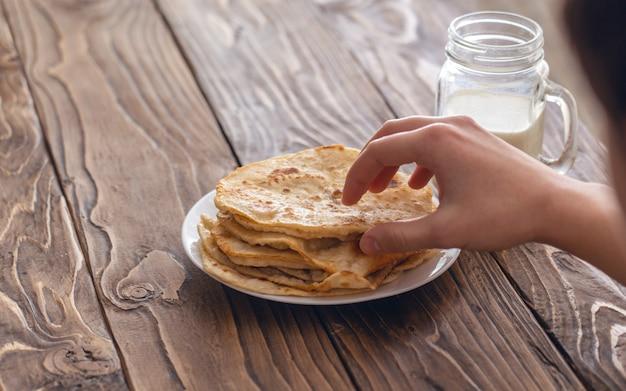 Un hombre está desayunando, una taza de leche y un plato de tortillas de maíz fritas sobre una mesa de madera con textura mirando por encima del hombro. espacio de copia de texto libre