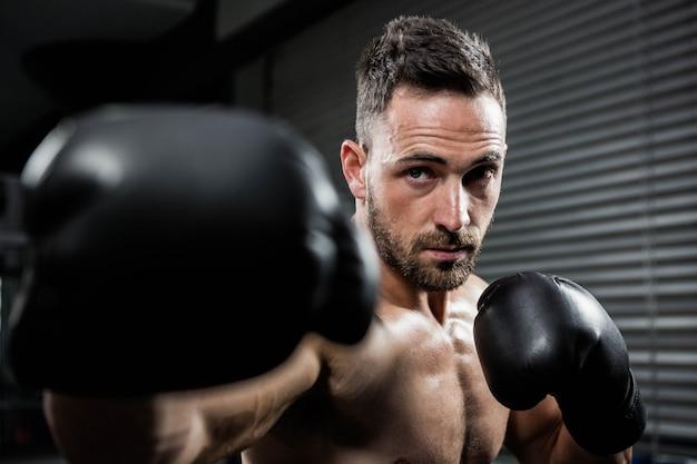 Hombre descamisado decidido con los guantes del boxe que golpean en el gimnasio del crossfit