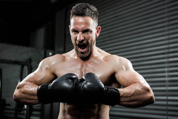 Hombre descamisado enojado con los guantes del boxe que grita en el gimnasio del crossfit