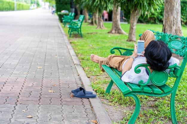 El hombre descansando en el banco del parque y leyendo noticias en el teléfono móvil.